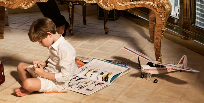 First kid Barron Trump in his room playing with his airplane toys and books.